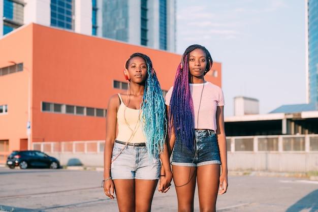 Zwei junge schöne schwarze schwestern, welche die hörende musikaufstellung der hände anhalten