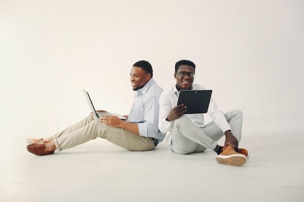 Zwei junge schwarze männer, die zusammenarbeiten und den laptop benutzen