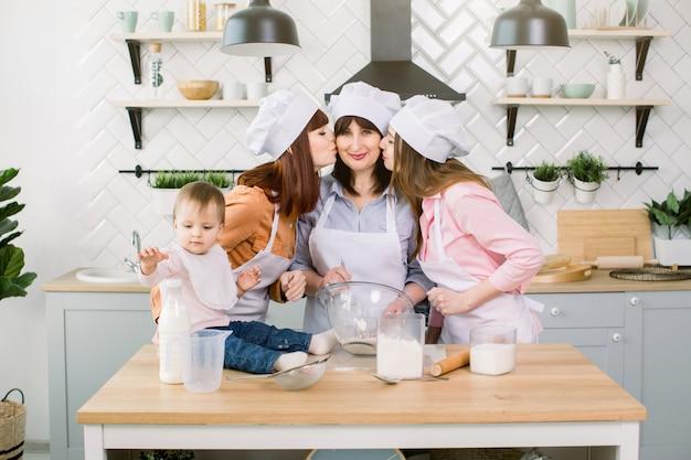 Zwei junge schwestern, großmutter und kleine tochter haben gute zeit in der küche. töchter küssen ihre mutter