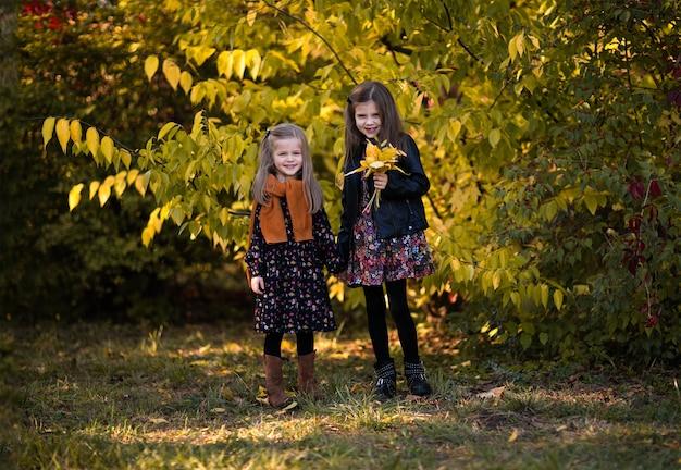 Zwei junge schwestern in herbstkleidern, lederjacke und rotem pullover posieren im herbstpark