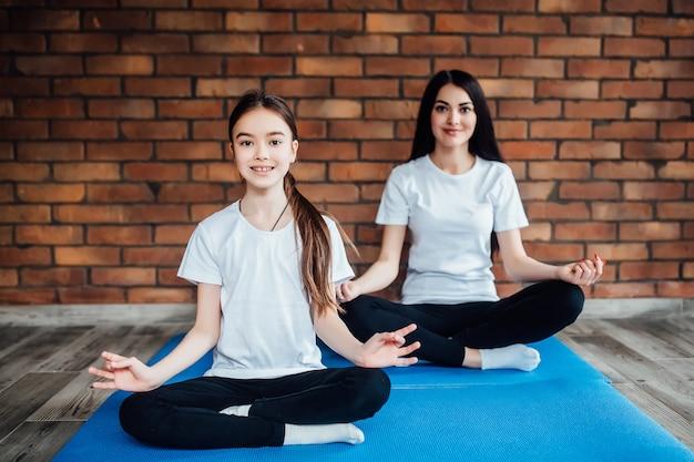 Zwei junge schwestern praktizieren yoga-position in einem indoor-fitnessstudio. gesundes und wellness-lifestyle-konzept