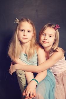 Zwei junge schwestern umarmen sich im hintergrund