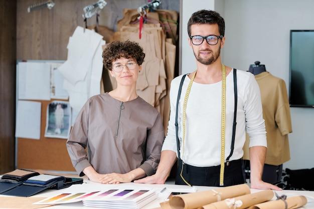 Zwei junge, selbstbewusste designer der neuen modekollektion erledigen ihre übliche arbeit am schreibtisch in der werkstatt