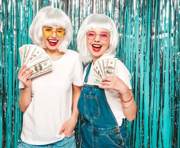 Zwei junge sexy hipster-mädchen in weißen perücken und roten lippen. schöne frauen, die dollar in händen halten, geben sommergeld aus