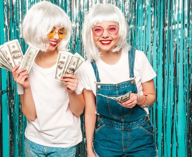 Zwei junge sexy hipster-mädchen in weißen perücken und roten lippen. schöne trendige frauen in sommerkleidung sommer, die spaß haben
