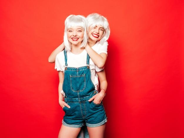 Zwei junge sexy lächelnde hipster-mädchen in den weißen perücken und in den roten lippen. schöne trendige frauen in der sommerkleidung