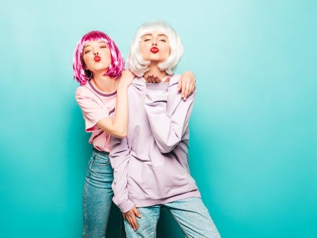 Zwei junge sexy lächelnde hipster-mädchen in perücken und roten lippen. schöne trendige frauen in sommerkleidung. sorglose modelle, die in der nähe der blauen wand im studio posieren, geben luftkuss