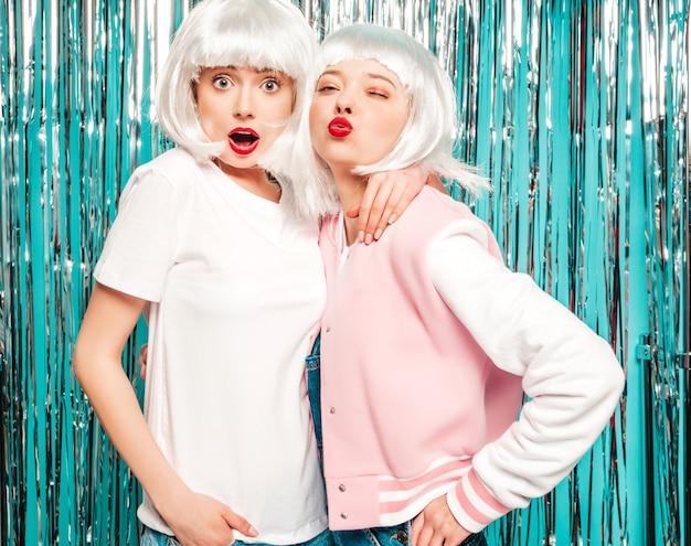 Zwei junge sexy lächelnde hipster-mädchen in weißen perücken und roten lippen. schöne trendige frauen im sommer kleidet sommer