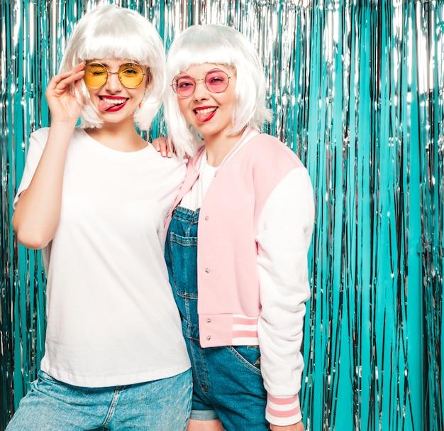 Zwei junge sexy lächelnde hipster-mädchen in weißen perücken und roten lippen. schöne trendige frauen in sommerkleidung. zeigen sie zungen in gläsern
