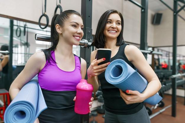 Zwei junge sportfrauen in der turnhalle sprechend lächelnd mit eignungsmatten