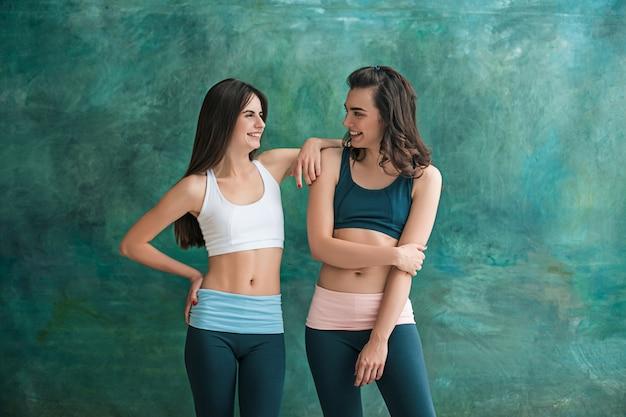 Zwei junge sportliche frauen, die im fitnessstudio posieren.