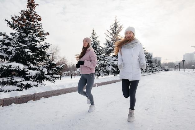 Zwei junge sportliche mädchen, die an einem sonnigen wintertag im park laufen. eine gesunde lebensweise.