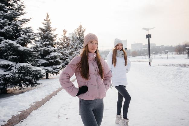 Zwei junge sportliche mädchen, die an einem sonnigen wintertag spazieren gehen und sport treiben. eine gesunde lebensweise.