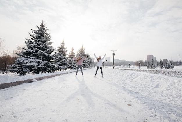 Zwei junge sportliche mädchen wärmen sich vor dem laufen an einem sonnigen wintertag auf. eine gesunde lebensweise.