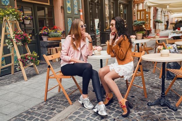 Zwei junge stilvolle frauen, die am café sitzen