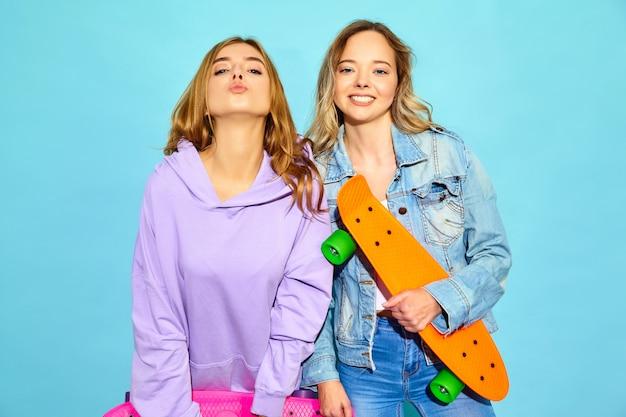 Zwei junge stilvolle lächelnde blonde frauen mit penny-skateboards. frauen in der sommerhippie-sportkleidung, die nahe blauer wand aufwirft. positive vorbilder