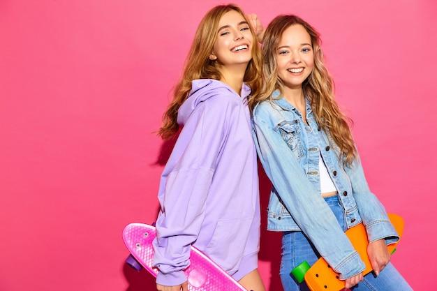 Zwei junge stilvolle lächelnde blonde frauen mit penny-skateboards. modelle in der sommerhippie-sportkleidung, die nahe rosa wand aufwirft. positive frauen werden verrückt