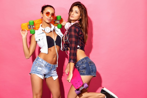 Zwei junge stilvolle lächelnde brunettefrauen mit pennyskateboards. modelle im sommerhippie kleidet die aufstellung nahe rosa wand im studio in der sonnenbrille mit kopfhörern