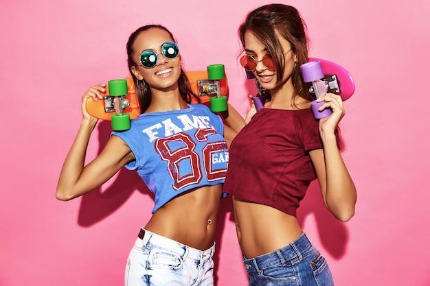 Zwei junge stilvolle lächelnde brunettefrauen mit pennyskateboards. modelle in der sommerhippie-sportkleidung, die nahe rosa wand in der sonnenbrille aufwirft. positive frau