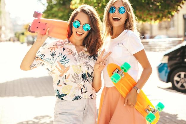 Zwei junge stilvolle lächelnde hippie-brünette und blonde frauenmodelle in sommer-hipster-kleidung mit penny-skateboard-aufstellung. überraschungsgesicht, emotionen