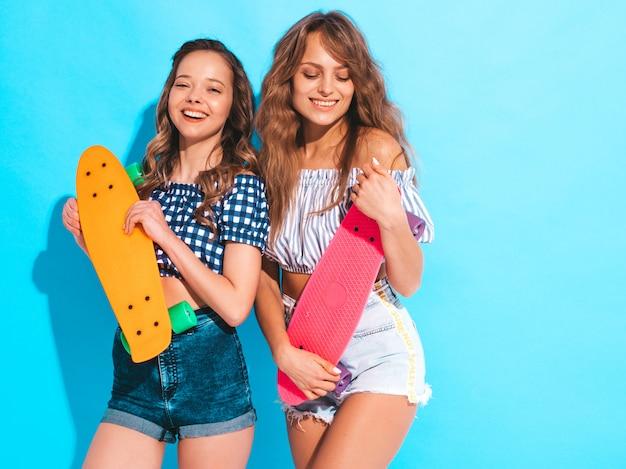 Zwei junge stilvolle lächelnde schöne mädchen mit bunten pennyskateboards. frau im karierten hemd des sommers kleidet die aufstellung. positive models, die spaß haben