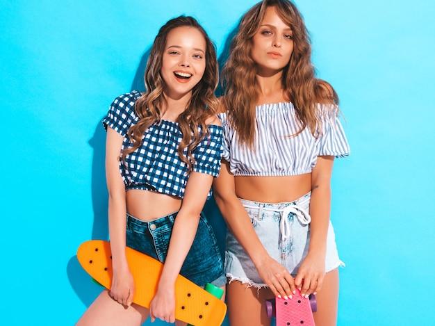 Zwei junge stilvolle lächelnde schöne mädchen mit bunten pennyskateboards. frauen in der karierten hemdkleidungsaufstellung des sommers. positive models, die spaß haben