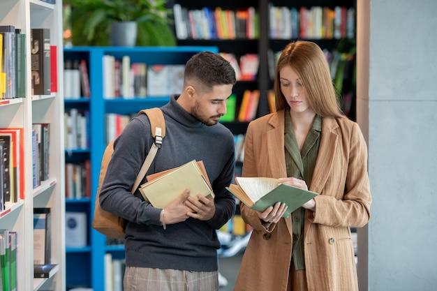 Zwei junge studenten, die bücher in der bibliothek oder im buchladen auswählen