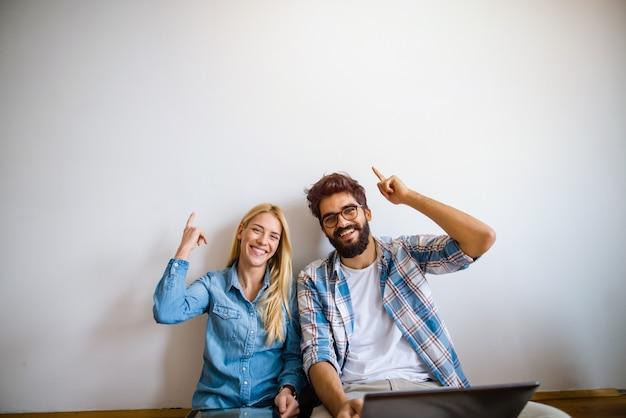 Zwei junge studenten sitzen auf einem boden und schauen in die kamera. mit einer hand, die mit dem finger auf den freien raum über ihnen zeigt.