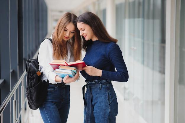Zwei junge studentinnen, die mit büchern und taschen im flur stehen