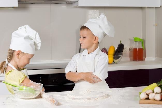 Zwei junge süße köche spielen in der heimischen küche.