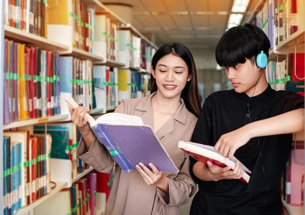 Zwei junge teenager lesen buch in der bibliothek zur prüfung