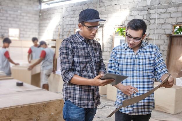 Zwei junge tischler diskutieren über möbelmaterialien