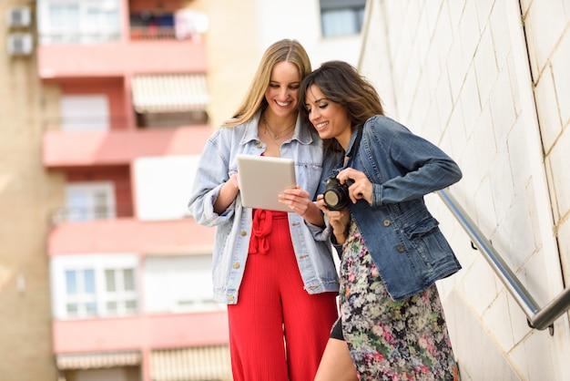 Zwei junge touristische frauen, die draußen karten mit digitaler tablette schauen.