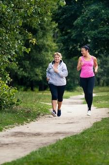 Zwei junge und alte frauen treiben sport und laufen im park