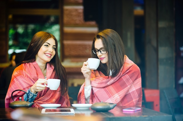 Zwei junge und schöne mädchen klatschen auf der terrasse bei einer tasse kaffee