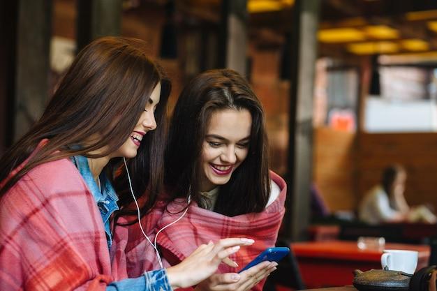 Zwei junge und schöne mädchen sitzen am tisch und hören musik mit einem smartphone