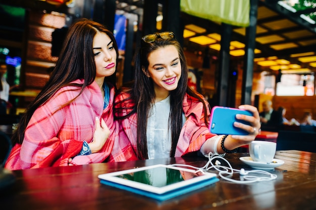 Zwei junge und schöne mädchen sitzen am tisch und machen selfie im café