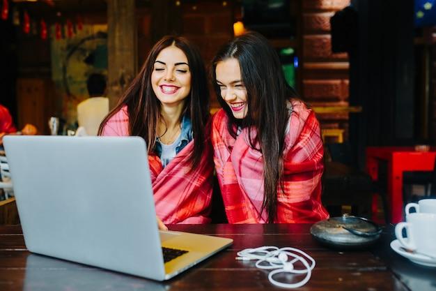 Zwei junge und schöne mädchen sitzen am tisch und suchen etwas im internet
