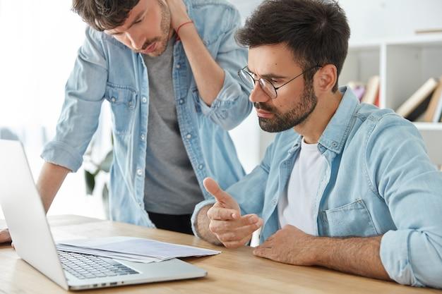 Zwei junge unternehmer arbeiten gemeinsam am finanzbericht, schauen sich die dokumente aufmerksam an