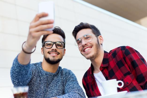 Zwei junge unternehmer, die ein selfie an der kaffeestube nehmen.