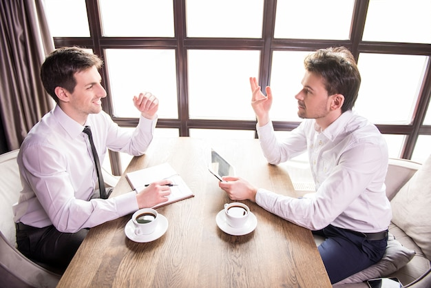 Zwei junge unternehmer diskutieren über die arbeit.