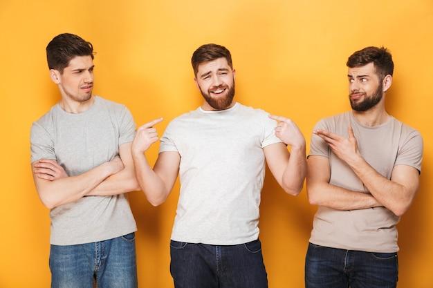 Zwei junge verwirrte männer, die ihren männlichen freund ansehen