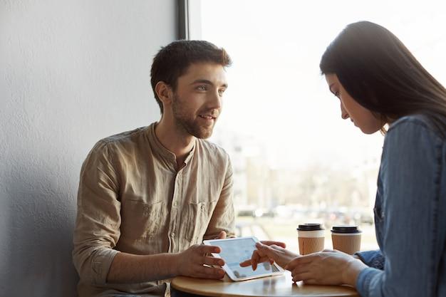 Zwei junge, vorsichtige unternehmer treffen sich beim kaffeetrinken, sprechen über ein zukünftiges start-up-projekt und schauen sich beispiele für das design von websites auf tablets in der cafeteria an. produktiver morgen bei bequemem platz