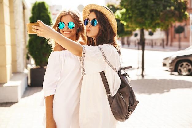 Zwei junge weibliche lächelnde hippie-brünette und blonde frauenmodelle im sonnigen sommertag in weißen hipster-kleidern, die selfie-fotos für soziale medien am telefon machen.