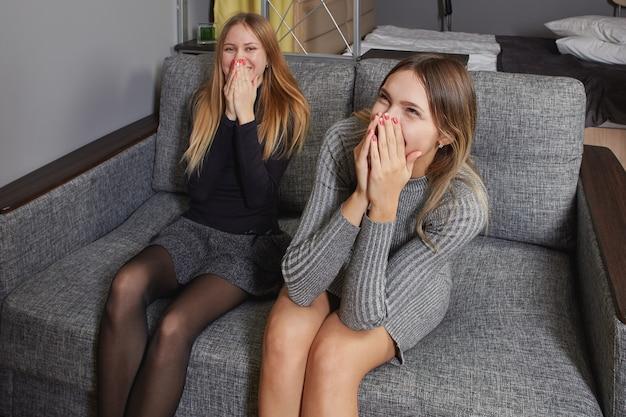 Zwei junge weiße frauen sehen sich eine lustige fernsehsendung an und lachen, wobei sie ihre gesichter mit den händen bedecken.