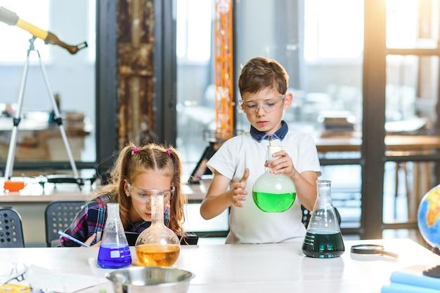 Zwei junge wissenschaftler in schutzgläsern führen interessante chemische experimente mit farbigen flüssigkeiten und trockeneis in bechern durch.