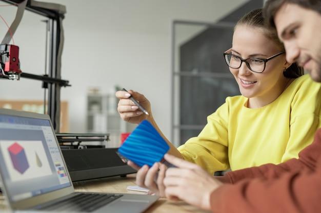 Zwei junge zeitgenössische designer diskutieren blaues plastikobjekt vor laptop, nachdem sie es auf 3d-drucker gedruckt haben