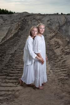 Zwei junge zwillinge mit langen haaren verbringen im sommer zeit miteinander im freien und posieren im sandsteinbruch in weißem kleid, rock, jacke