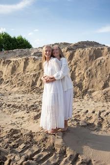 Zwei junge zwillinge mit langen haaren verbringen im sommer zeit miteinander im freien und umarmen den sandsteinbruch in weißem kleid, rock und jacke