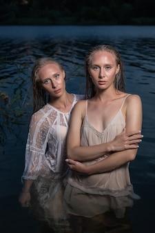 Zwei junge zwillingsschwestern, die in der sommernacht in leichten kleidern im wasser des sees aufwerfen